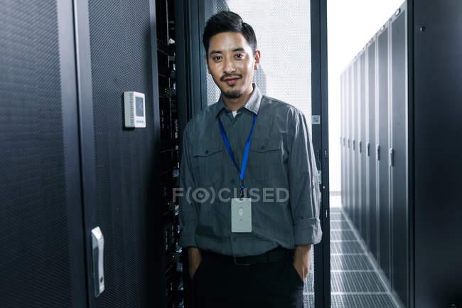 Красивый инженер-мужчина, стоящий и улыбающийся перед камерой в комнате технического обслуживания — стоковое фото