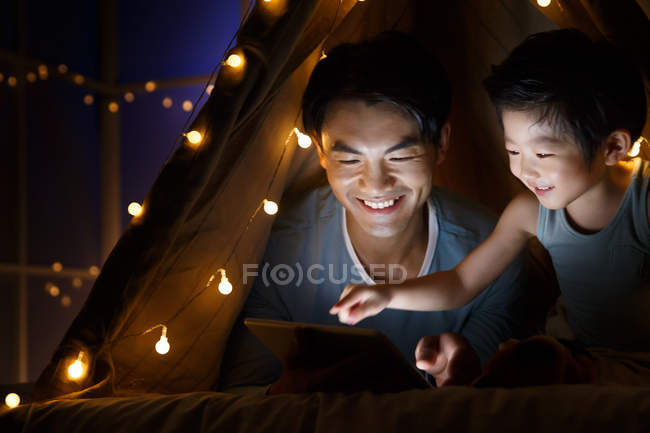 Happy asian father and preschooler son watching something on tablet in tent at home — Stock Photo