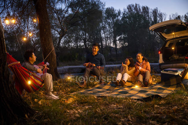 Man playing guitar for three asian friends at camping in autumnal evening forest — Stock Photo