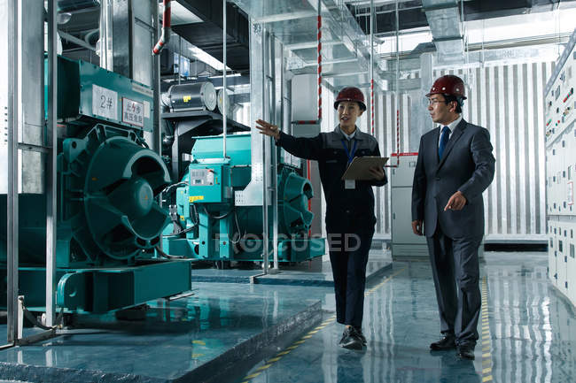 Chinese engineers in hard hats working together in the factory inspection — Stock Photo