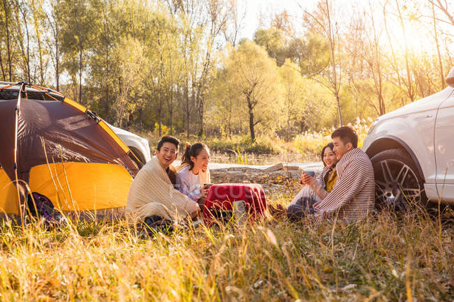 Four happy asian friends drinking tea and talking at camping place in autumnal forest — Stock Photo