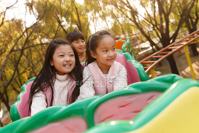 Happy boy and girls playing together on roller coaster in park — Foto stock