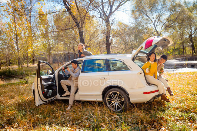 Male and female asian friends sitting in car in autumnal forest — Stock Photo