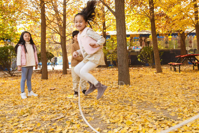 Happy boy and girls playing together and jumping in autumn park — Stock Photo