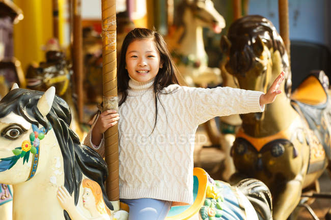 Adorable happy little girl playing with carousel — Stock Photo
