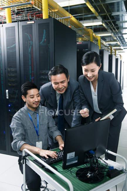 Улыбающийся технический персонал, работающий на компьютере и в ремонтной мастерской. — стоковое фото