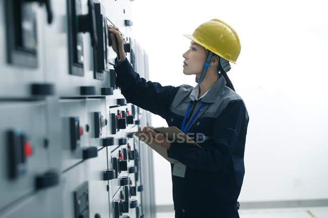 Side view of female technician in yellow helmet working in factory — Stock Photo