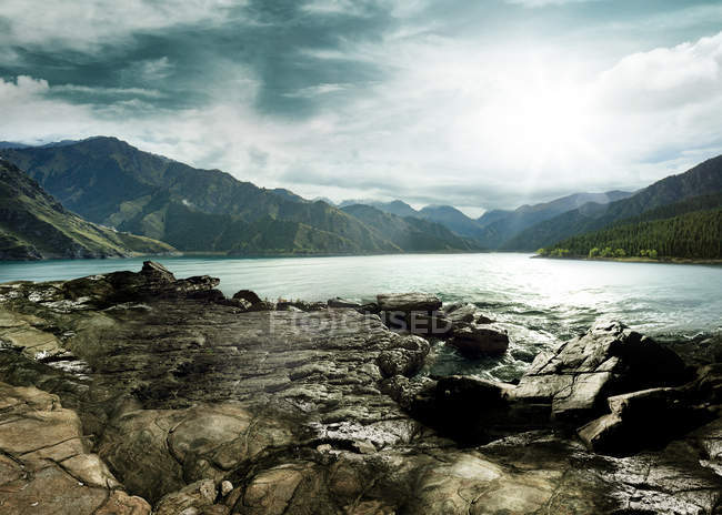 Amazing mountain landscape with lake and clouds in sky — Stock Photo