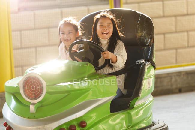 Гарні веселі китайські дівчата їздять на машині і бавляться разом на ігровому майданчику. — стокове фото