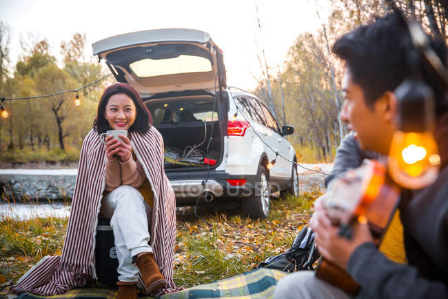 Happy asian boyfriend playing guitar for girlfriend in autumnal forest — Stock Photo