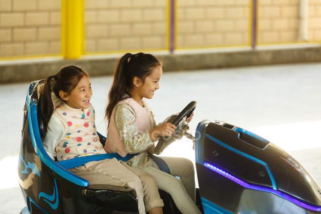 Чудові приємні китайські дівчата їздять автомобілем і бавляться разом на дитячому майданчику. — стокове фото