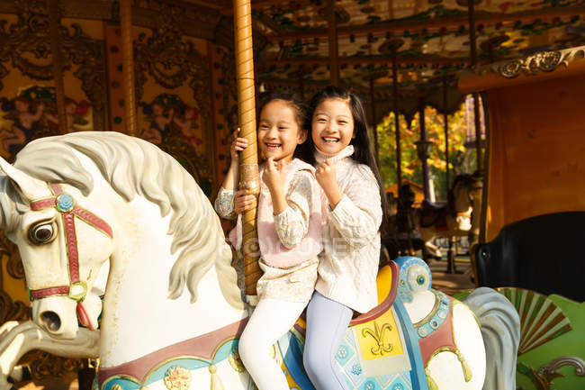 Cute cheerful little girls playing with carousel — Stock Photo