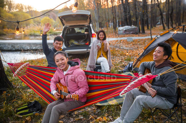 Asian friends playing guitar and ukulele at camping in autumnal forest — Stock Photo