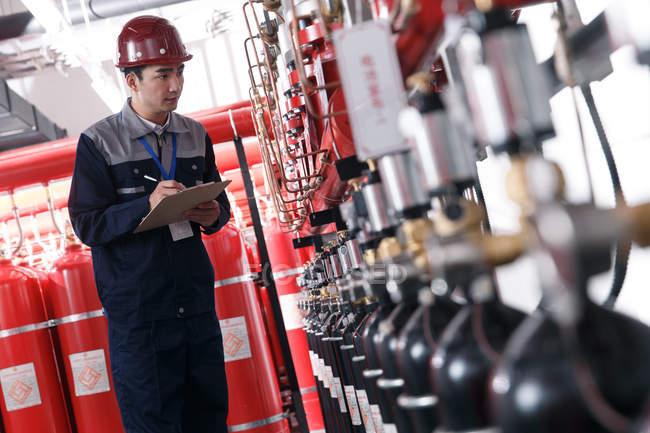 Ingeniero masculino profesional en el sombrero duro que trabaja en la inspección de la sala de control de incendios de fábrica - foto de stock
