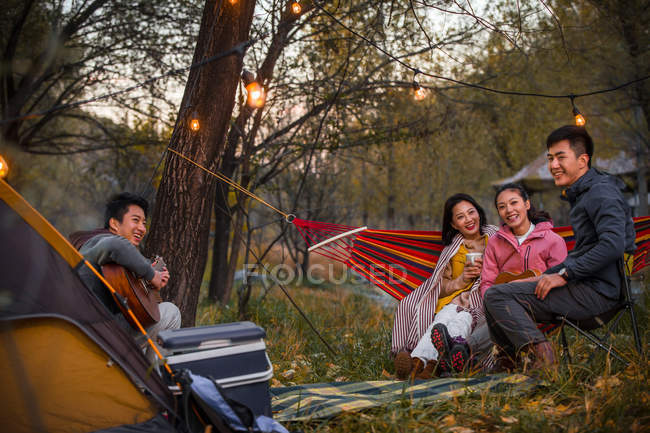 Man playing guitar for asian friends in autumnal forest — Stock Photo