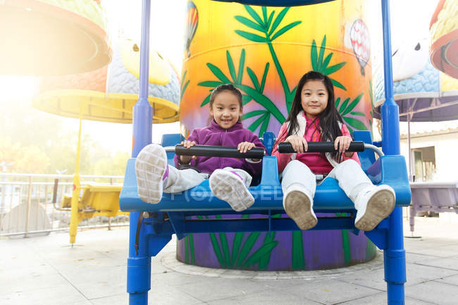 Happy girls playing together on roller coaster in park — Stock Photo