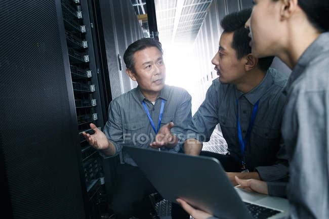 Персонал, работающий с ноутбуком в ремонтной комнате — стоковое фото