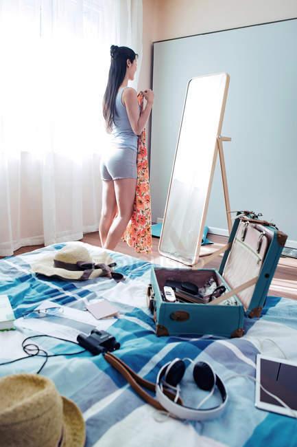 Belle jeune femme retenant la robe et regardant le miroir à la maison — Photo de stock