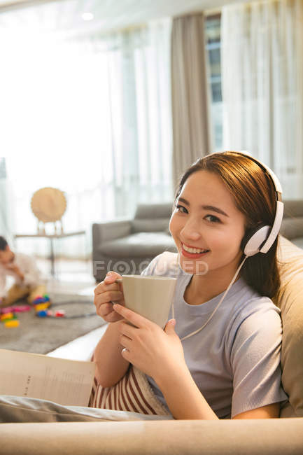 Chinese woman in headphones holding cup and smiling at camera while son playing with toys behind at home — Stock Photo