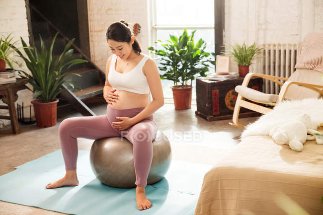 High angle view of smiling young pregnant woman in sportswear sitting on fit ball at home — Stock Photo