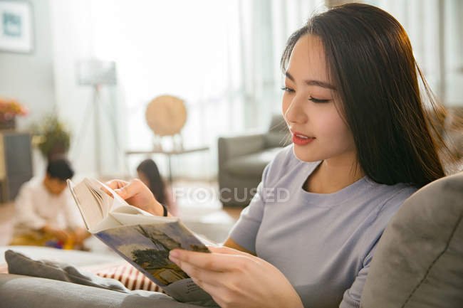 Smiling young woman reading book while children playing behind on carpet — Stock Photo