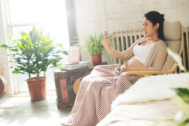 Вид сбоку счастливой молодой беременной женщины, сидящей в кресле и использующей смартфон — стоковое фото