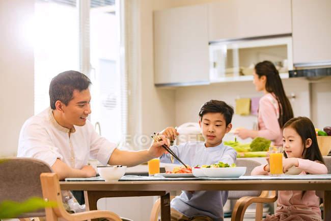 Vater mit Kindern am Tisch sitzen und essen, Mutter kocht in der Küche — Stockfoto