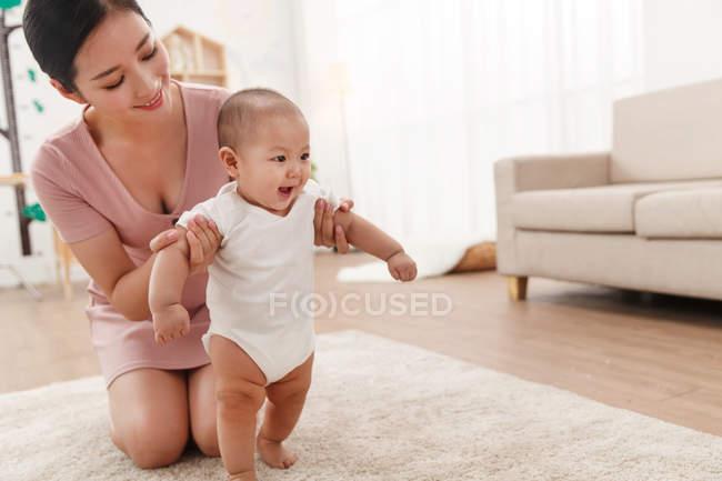 Щасливий молода мати допомагає чарівні дитини стоячи на килимі — стокове фото