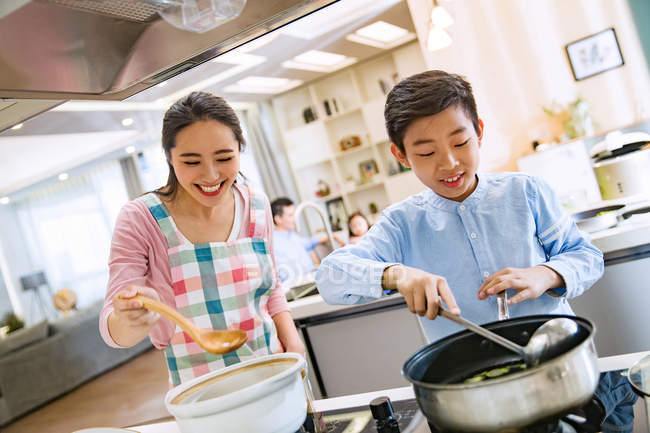 Happy asian mother with son cooking together in kitchen — Stock Photo