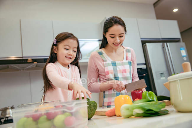 Happy young asian mother and adorable little daughter cooking together in kitchen — Stock Photo
