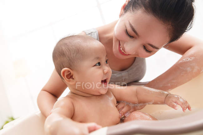 Happy young mother bathing adorable infant baby at home — Stock Photo