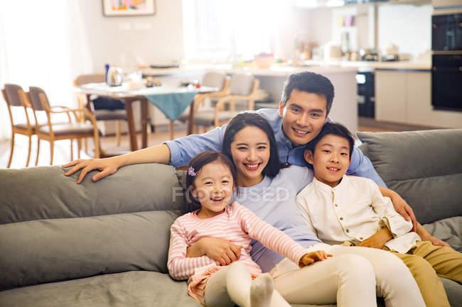 Щаслива Азіатська сім'я з двома дітьми сидять разом на дивані і посміхаючись на камеру — стокове фото