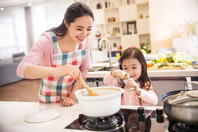 Mãe asiática feliz e filha cozinhar sopa juntos na cozinha — Fotografia de Stock