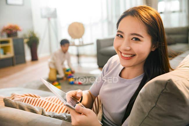 Happy молода Азіатська жінка з використанням цифрової планшета і посміхаючись камери, а син грає з іграшками позаду вдома — стокове фото