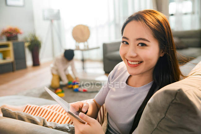 Happy young asian woman using digital tablet and smiling at camera while son playing with toys behind at home — Stock Photo