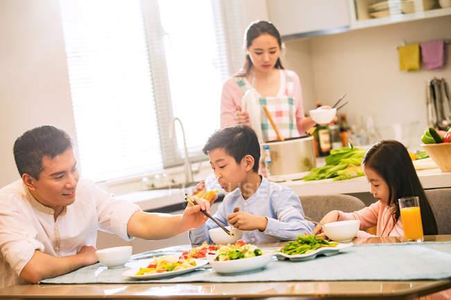 Glückliche chinesische Familie mit zwei Kindern am Tisch sitzen und essen zusammen zu Hause — Stockfoto