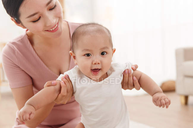 Happy young mother with carrying adorable infant baby at home, cropped shot — Stock Photo