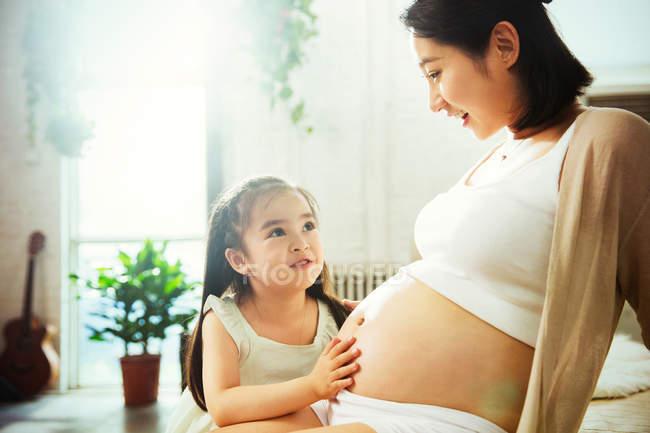 Прелестная счастливая маленькая девочка трогает живот и смотрит на беременную мать — стоковое фото