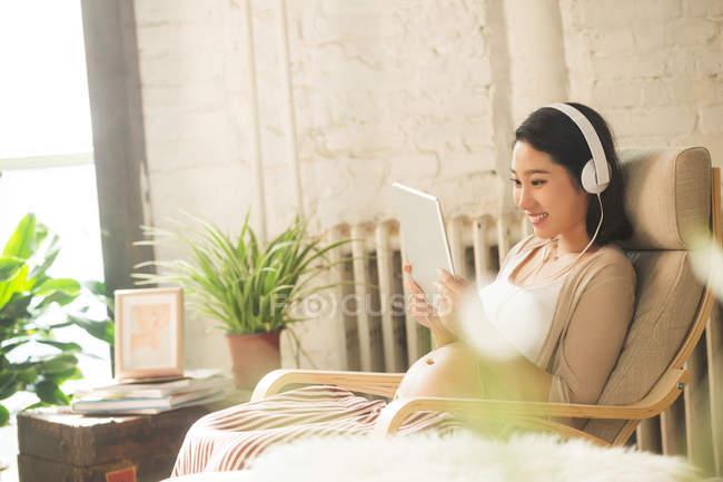 Sorrindo jovem grávida em fones de ouvido usando tablet digital em casa — Fotografia de Stock