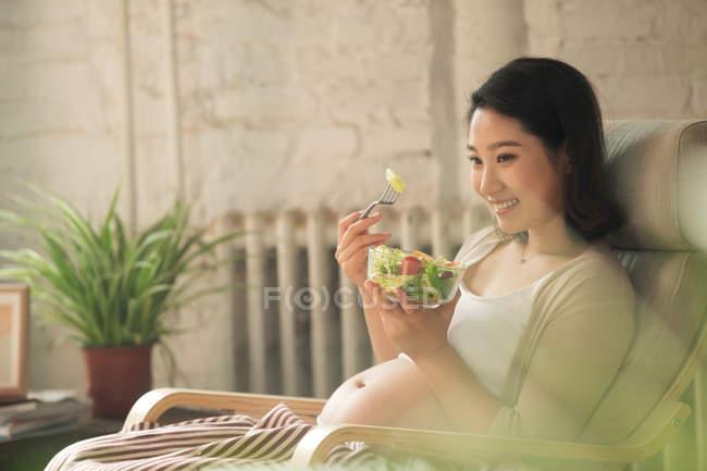Lächelnde junge Schwangere, die zu Hause gesunden Gemüsesalat isst, selektiver Fokus — Stockfoto