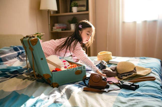 Adorabile poco asiatico ragazza imballaggio valigia su letto — Foto stock