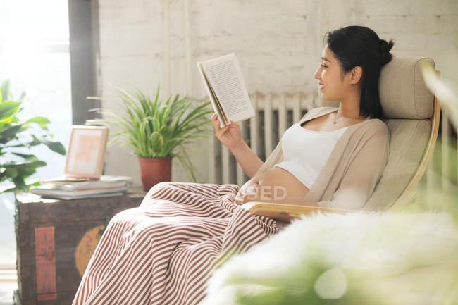 Vista laterale di sorridere giovane donna incinta seduta sulla sedia e libro di lettura, messa a fuoco selettiva — Foto stock