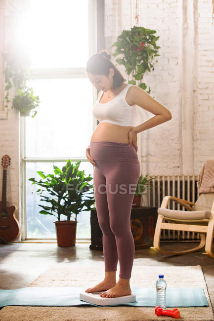 Young barefoot pregnant woman standing on scales and looking down — Stock Photo