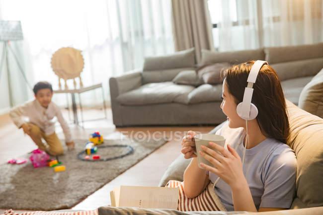 Молодая женщина в наушниках держит чашку и смотрит на сына, играющего с игрушками на ковре — стоковое фото