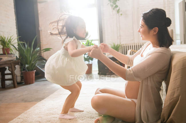 Вид сбоку на беременную молодую мать и симпатичную маленькую дочку, держащуюся за руки и играющую дома — стоковое фото
