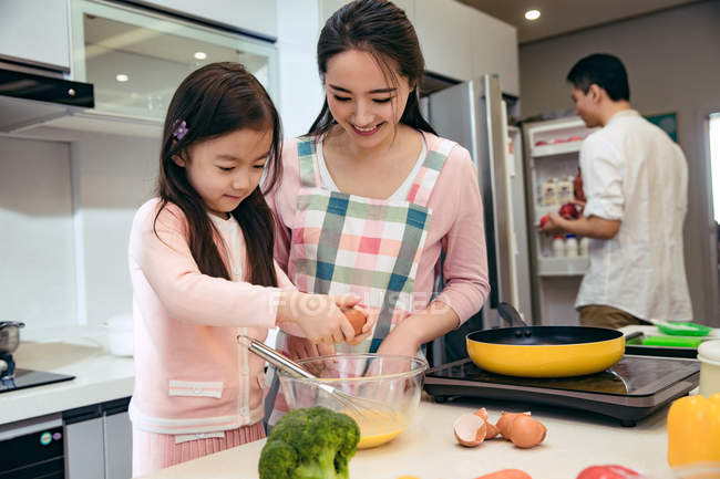Happy mother and daughter cooking together while father opening refrigerator behind in kitchen — Stock Photo
