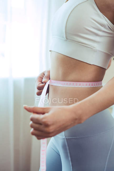 Cropped shot of sporty young woman measuring waist with tape — Stock Photo