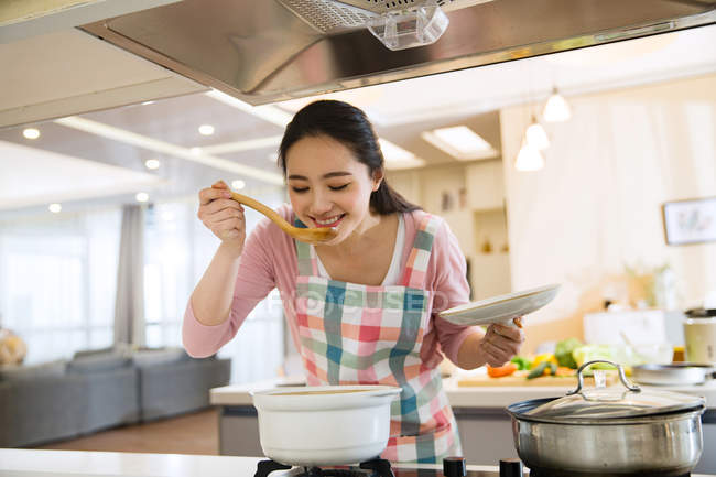 Smiling young woman cooking and tasting dish in kitchen — стокове фото