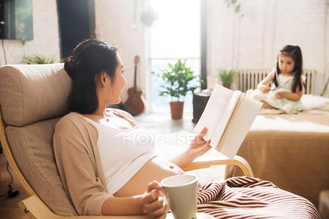 Молодая беременная мать читает книгу и смотрит на маленькую дочь, играющую дома — стоковое фото