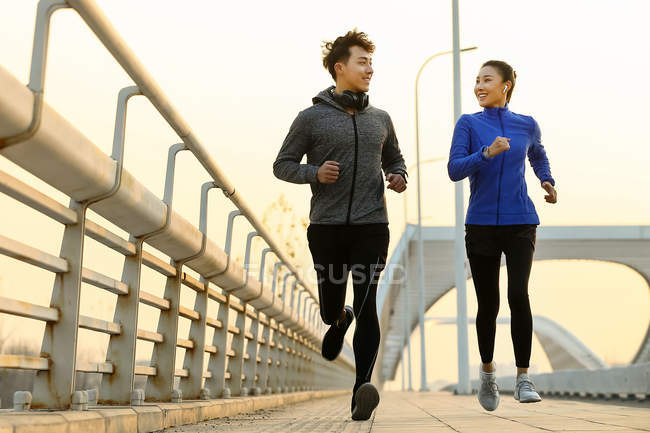 Happy sporty young asian couple smiling each other and running together on bridge — Stock Photo